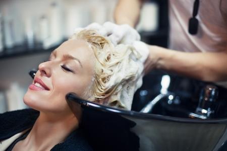 Lachende vrouw met haar haren wassen bij de kapper.