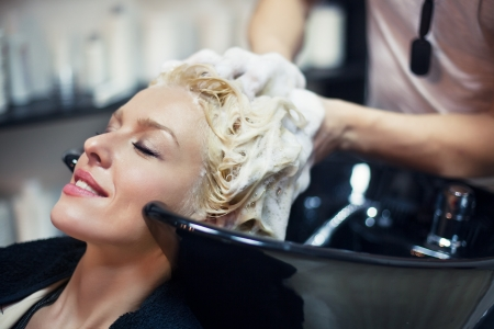 champu: Mujer sonriente con el pelo lavado en la peluquería. Foto de archivo