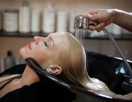 Lachende vrouw met haar haren wassen bij de kapper. Stockfoto