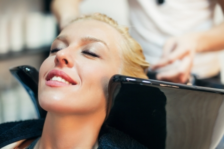Smiling woman having her hair washed at the hairdressers. photo