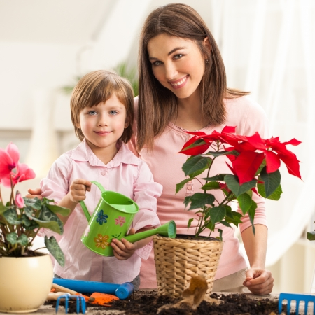 Mother and daughter watering plants together. photo