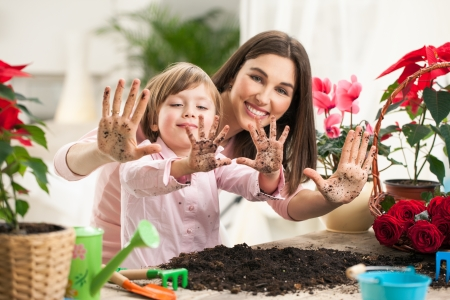 family gardening: Mother and daughter showing dirty hands after gardening together. Stock Photo