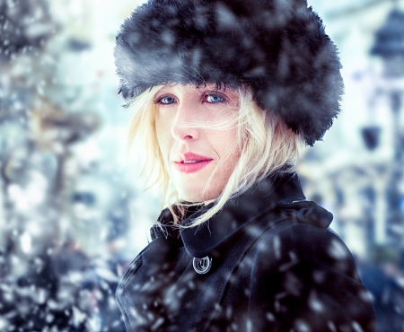 Beautiful mid-adult woman wearing a fur hat standing outdoors on a winter day. photo
