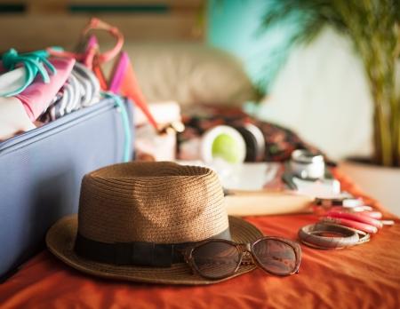 El dormitorio de la mujer llena de cosas listas para ser tomadas en vacaciones de verano. Foto de archivo