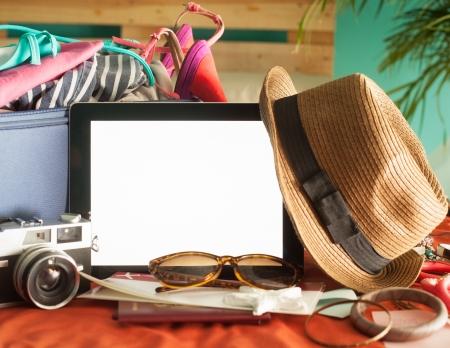mujer con maleta: Tableta digital, billete de avi�n y otros accesorios listos para ser embalados para vacaciones de verano. Foto de archivo