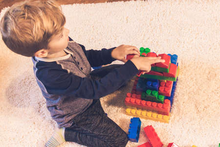 Little boy building with toy blocks and playing on the carpet at home.