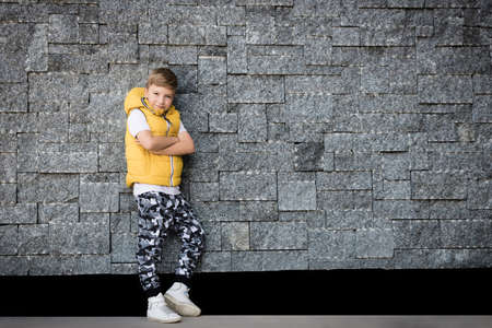 Happy boy standing with crossed arms and looking at camera while leaning on a wall. Copy space.