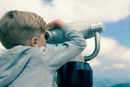 Small boy exploring the sky through a telescope.