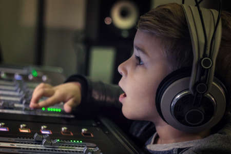 Close up of boy with headphone adjusting volume on electronic sound mixer in recording studio.