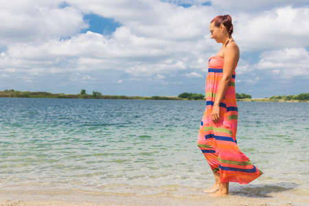 Carefree woman enjoying in summer day while walking through sea at the beach. Copy space.