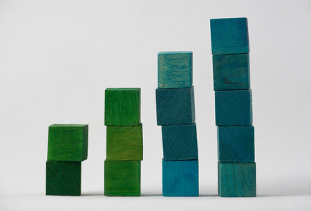 Green and blue stacked coloured wooden cubes isolated on white background