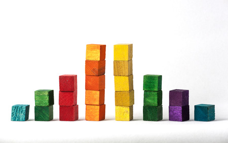 Blue, green, red, orange, yellow and purple stacked wooden cubes isolated on white background.