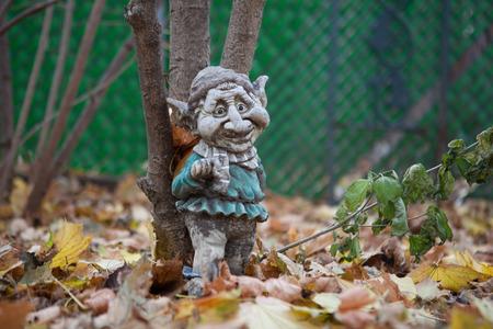 gnomos: Resistido Enano de jardín apoyada en un árbol Foto de archivo