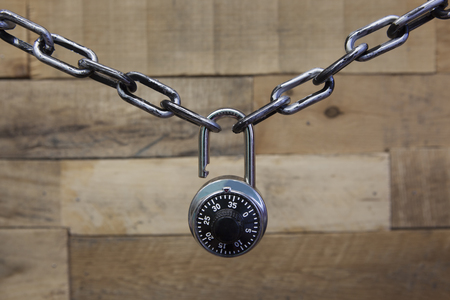 Security Series Chained Black Padlock on a Wooden patterned background Stock Photo
