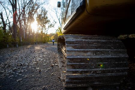 First person view of a tractor parked in a local park with an unidentified woman walking towards the sunset Stock Photo