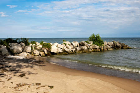 Clear Summer Afternoon Beach with Rock Outlet