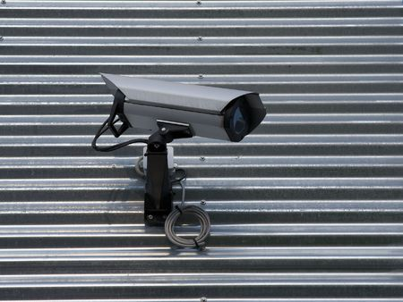 testify: Surveillance video camera attached on a wall of a building