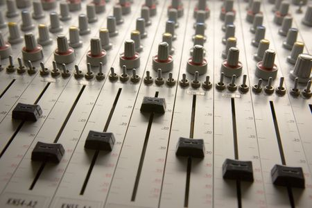 Professional audio mixing board with multiple channel faders and adjusting knobs Stock Photo