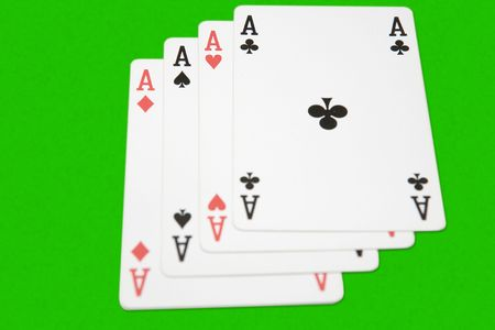 risky situation: Winning playing cards, four aces, on green background