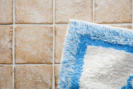 Bathroom interior detail in an elevated perspective - cermic tile floor and a bath rug Stock Photo
