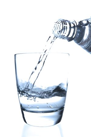 Pouring water from a bottle to a half filled glass
