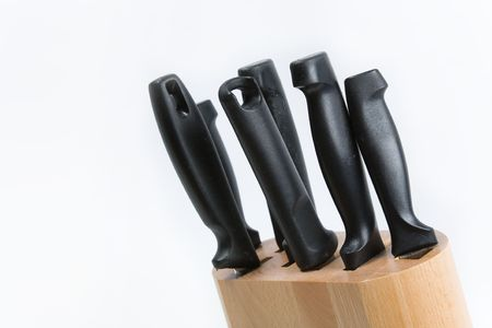 arranged: Kitchen knives in a wooden block on a white background