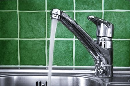 Kitchen water tap and green tiles Stock Photo