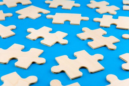 Wooden puzzle pieces on blue background Stock Photo - 2517726