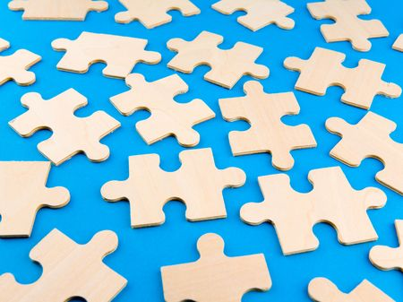 Wooden puzzle pieces on blue background Stock Photo - 2517731