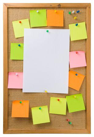 Notas Adhesivas y hoja de papel adjunta a un tablón de anuncios
