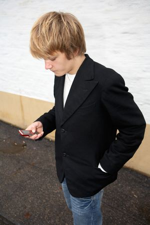 Teenage boy text messaging with mobile phone in street Stock Photo - 3448132