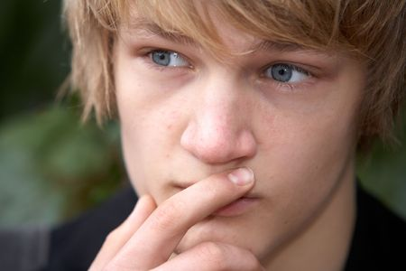 only one teenage boy: Teenage boy contemplating in city park, close-up Stock Photo