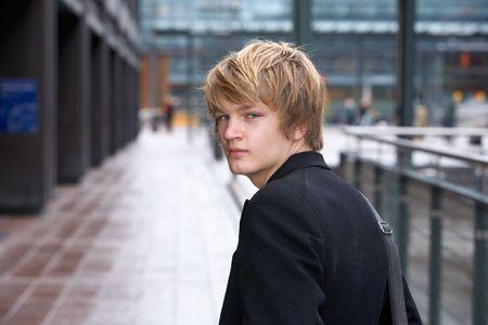 away: Teenage boy looking back over his shoulder in city
