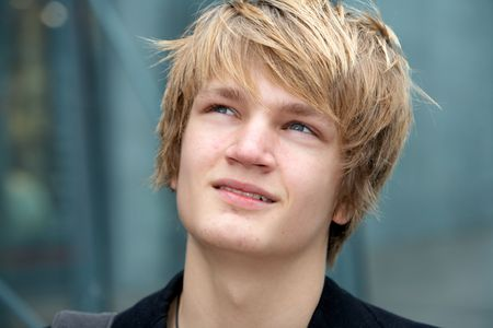 only one teenage boy: Close-up of teenage boy smiling in urban environment