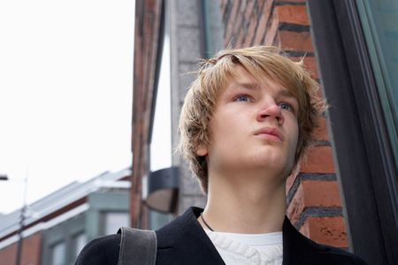 Teenage boy standing by building in street, low angle Stock Photo - 3465948