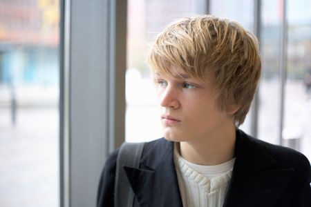 Teenage boy looking out window in urban environment, interior photo
