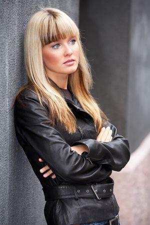 mujeres tristes: Joven mujer apoy�ndose a la pared en la acera, mirando lejos  Foto de archivo