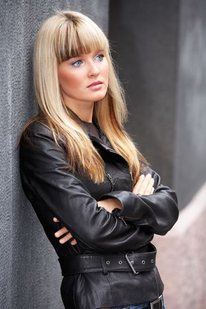 Young woman leaning to wall on sidewalk, looking away Stock Photo - 3466116