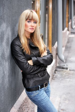Young woman leaning to wall on sidewalk, arms crossed, looking at camera Stock Photo