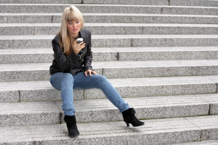 Young woman looking at mobile phone, sitting on stairway Stock Photo - 3472972