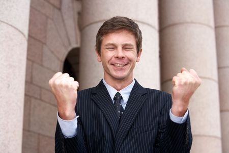 winning location: Man cheering outside building Stock Photo
