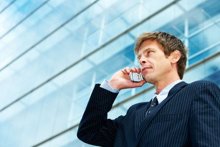 businessman phone: Man outside office building, using cell phone Stock Photo