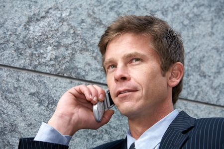 Man on cell phone by building wall, low angle close-up Stock Photo - 3493928