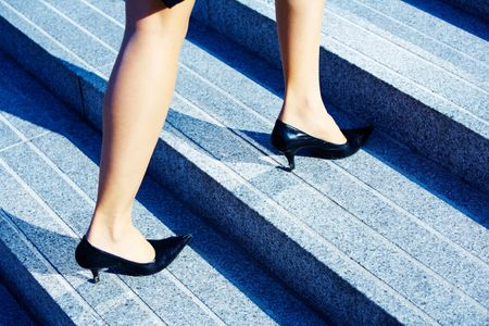 Businesswoman walking up stairs to higher level photo
