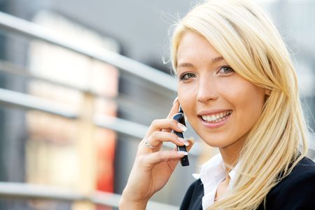 Businesswoman using a mobile phone and smiling Stock Photo - 3489330