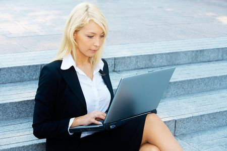 Young businesswoman sitting on stairway, using laptop computer Stock Photo