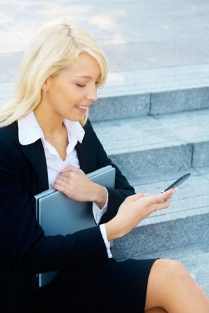 Young businesswoman sitting on stairway, looking at cell phone photo
