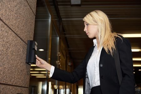 Young businesswoman entering access code at building entrance