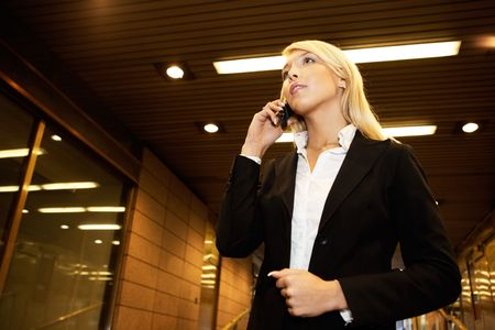 passageway: Young businesswoman using mobile phone in passageway of office building Stock Photo