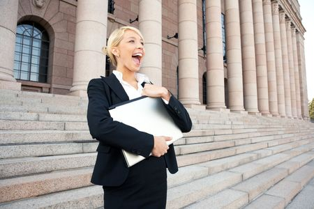 Happy young businesswoman holding laptop computer outside building Stock Photo - 3505269